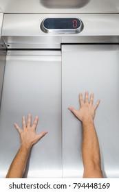 Man hands try to stop and prevent closing elevator door