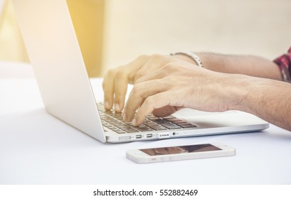 Man hands typing on laptop on white table with mobile, selective focus