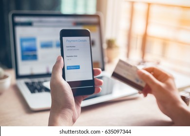 Man hands using smartphone and laptop computer for online shopping at home, Hand holding mobile phone with Payment Detail page display and credit card, online shopping concepts
