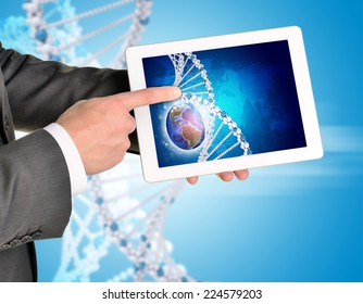 Man hands using tablet pc. Image of Earth and DNA helix on tablet screen. Element of this image furnished by NASA