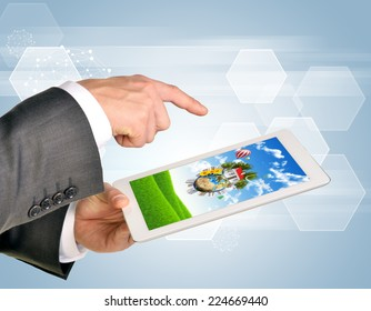 Man hands using tablet pc. Image of Earth and house on tablet screen. Element of this image furnished by NASA