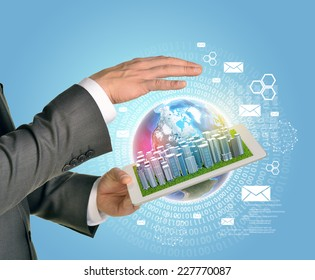 Man hands using tablet pc. Business city on touch screen. Earth as backdrop. Element of this image furnished by NASA
