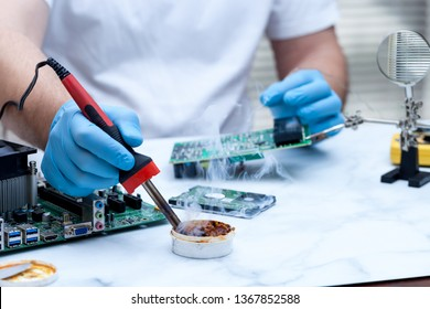 Man hands wearing gloves solders and verifies computer circuit board using soldering iron and multi meter