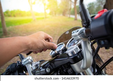 Man hands wearing motorcycle gloves are inserting the key and starting the engine. Motorcycle ignition action.