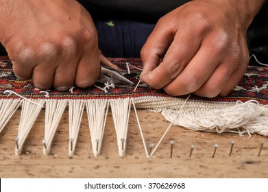 Man hands weaving a traditional handmade carpet in Isfahan Iran