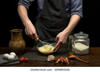 Man hands are whipping by whisk to make dough. black background