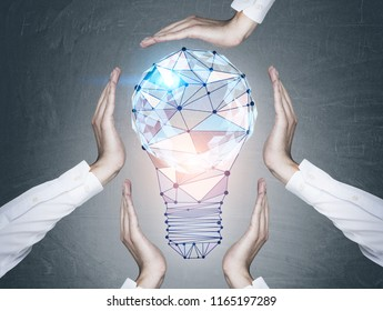 Man hands in white shirts protecting a large glowing polygonal light bulb over a blackboard background. Idea and copyright concept. Toned image