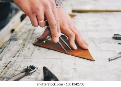 Man hands working with leather using crafting DIY tools