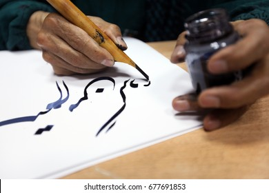 man hands writing arabic calligraphy with ink