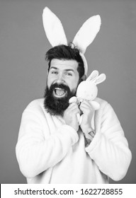 Man handsome face wear white bunny ears. Easter bunny. White bunny symbol of easter holiday. Soft and tender. Guy with bunny or rabbit ears on violet background. Enjoy tenderness. Childhood memories.