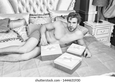 Man handsome lover and gift. Surprise for sweetheart. Gifts for darling. Birthday morning. Romantic surprise. Valentines day celebration. Sexy surprise for female. Man in luxury bedroom with gift box.