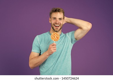 Man handsome macho eat big colorful sweet lollipop. Taste of childhood. Man bearded adult likes lollipop. Sweet tooth concept. Sugar harmful for health. Guy hold lollipop candy violet background.