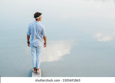 Man handsome stands on wooden bridge and looks at the water reflex of blue sky. Shoot from the back. Concept of freedom relaxation. Place for text or advertising