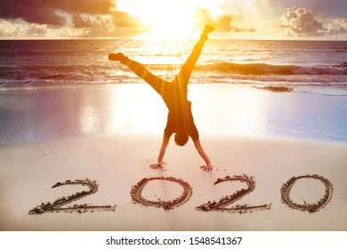 man handstand on the beach.happy new year 2020 concept
