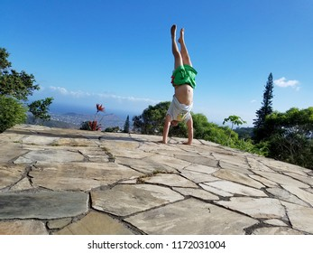 Man Handstanding on top mountain with diamondhead in distance on of Oahu, Hawaii.