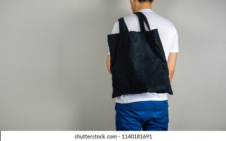 Man hanging black bag in the back