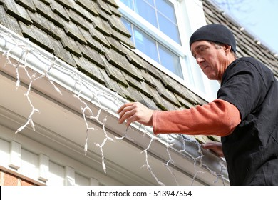 a man hanging Christmas lights on the exterior of a house