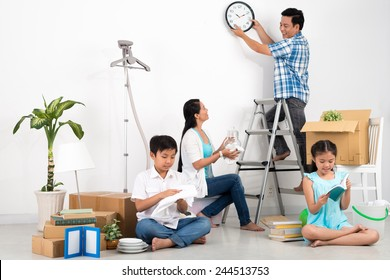 Man hanging clock on the wall while his wife and children unpacking