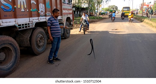 man hanging dead snake by stick on road at district Katni Madhya Pradesh in India shot captured on sep 2019