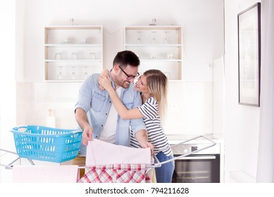 Man hanging laundry on clothing rack and girlfriend hugging him. Togetherness in housework