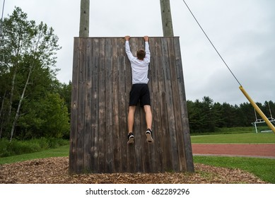 Man hanging from an obstacle wall.