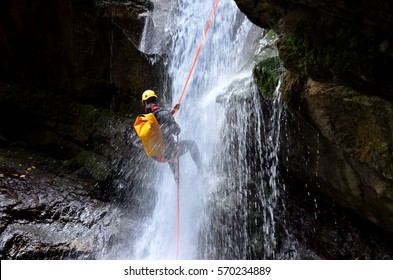 Man hanging of a rope at the bottom of a waterfall