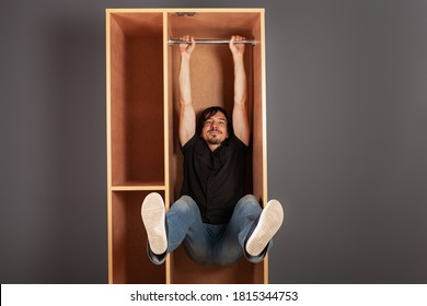 A man hangs in a cupboard on a pipe, funny, a test of the closet for strength.