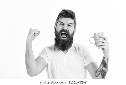Man with happy face stretching try to awake with cup of coffee. Hipster with beard holds mug, energetic and successful macho. Man full of energy in morning, white background. Energetic man concept.