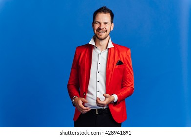 Man with happy facial expression in a red jacket on a blue background