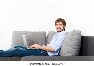 man happy smile with laptop lying on sofa at home, young guy surfing on computer, with copy space on white wall