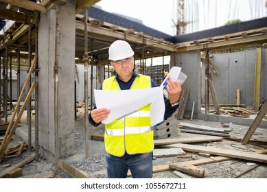 Man in hardhat and green jacket posing on building site