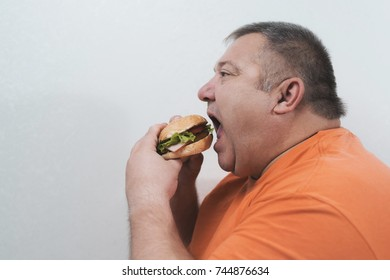A man has bulimia. He is really hungry and he is eating unhealthy food. He has overweight, and he is going to eat hamburger.