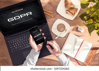 "Man has ""GDPR"" message on his smartphone and laptop display. Conception of  General Data Protection Regulation in EU law. Interface created in graphic program"