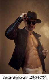 A man has a hat on his head and in a jacket on a naked torso