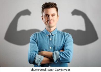 Man has shadow with strong arms