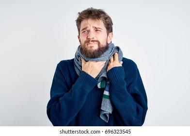 A man has a sore throat, a neck in a scarf, flu
