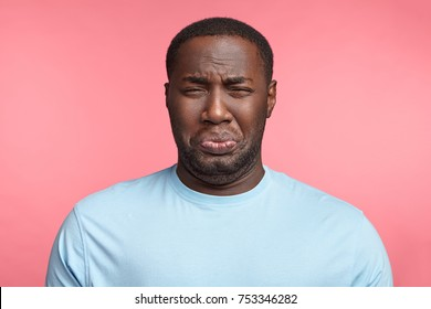 man has sorrorful miserable expression being depressed after fired on work, cries, has stressful situation, dressed casually, isolated over pink background. Plump unshaven African man in panic