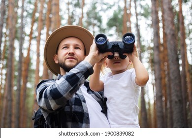 Man in a hat and a backpack and a child look through binoculars while hiking in the forest. Family hike to the mountains or forest.