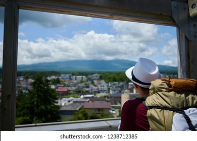 Man with hat and backpack looks onto cloud hid mount fujiyama and the city of fuyijoshida in front of it from the rooftop of a viewpoint