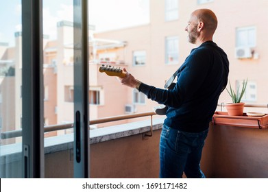 Man in a hat with a beard plays the guitar on the balcony in the summer. Side view. Covid - 19