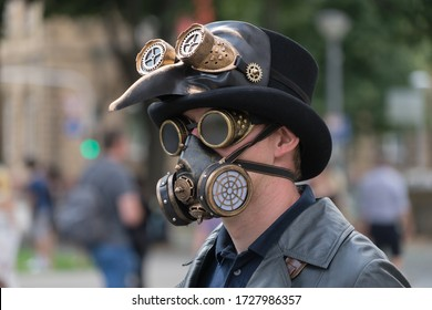 Man with hat, breather, protection goggles and black death mask on the street