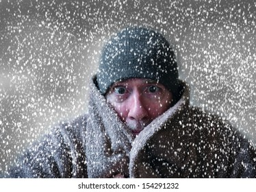 Man in hat and coat shivering in Christmas snowstorm with cloudy skies and snowflakes blowing in wind funny