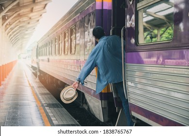 A man with hat holding handrail in train at the open door. People travel local transport.