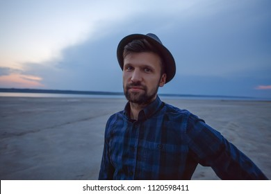 Man in hat is looking to camera. pretty man wears shirt in cage, guy in hat, stylish clothes, hipster, traveler, loner, handsome bearded guy, outdoor portrait, man by the lake, sunrise, summer concept