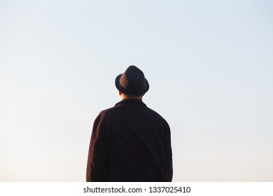 Man with hat looking at clear sky