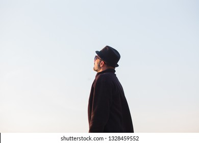Man with hat looking at sky