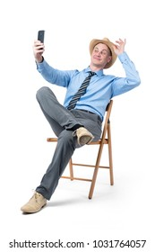 Man in hat makes selfie on smartphone, sitting on a chair isolated on white background