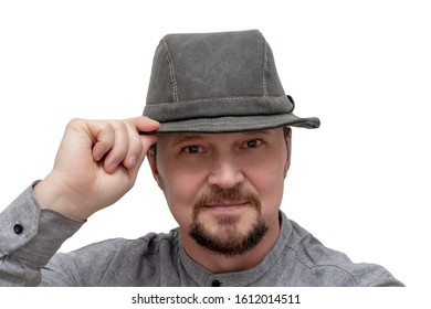 A man in a hat with a mustache and beard touches the hat on his head with his hand.