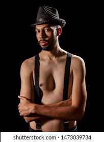 Man with hat on his head with suspender on his naked body.
