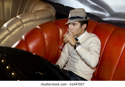 Man with hat seated on sofa in night club, with a glass of wine on the hand
